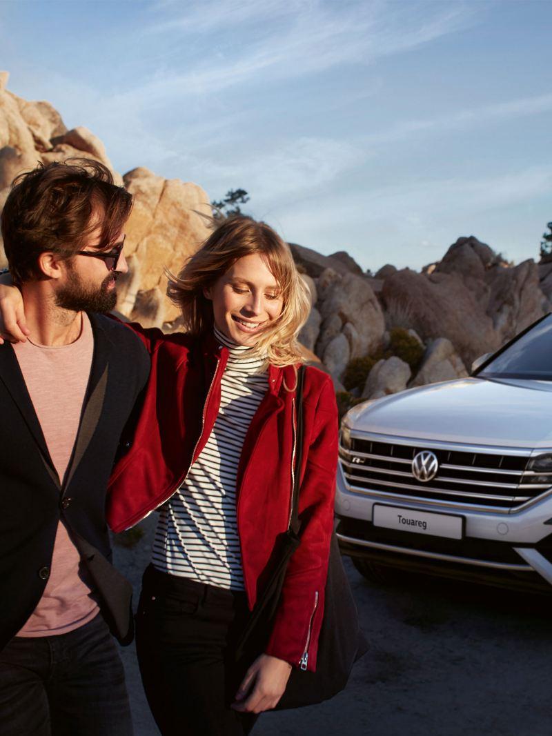 ragazzi abbracciati felici in montagna davanti a Volkswagen Touareg SUV