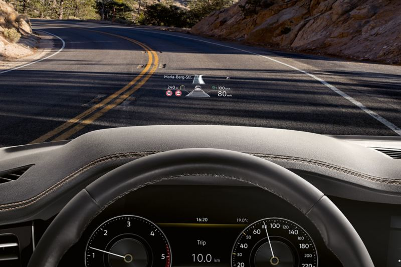View on the street through the windshield of the VW Touareg One Million; in front is the display of the Head-up-Display