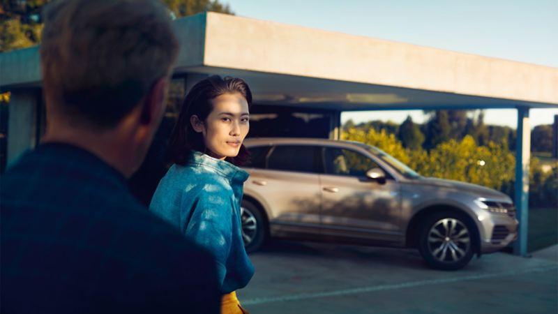 Kvinne ser på mann med Volkswagen VW Touareg i bakgrunnen