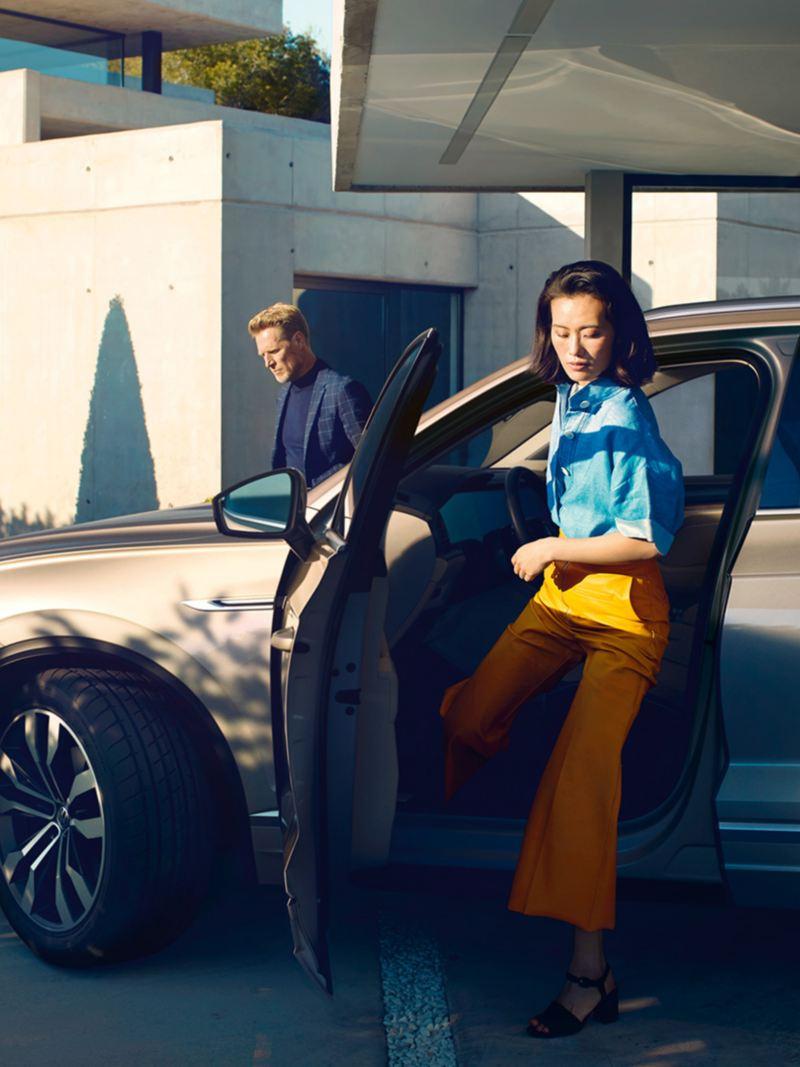 Kvinne stiger ut av Volkswagen VW Touareg, mann står bak