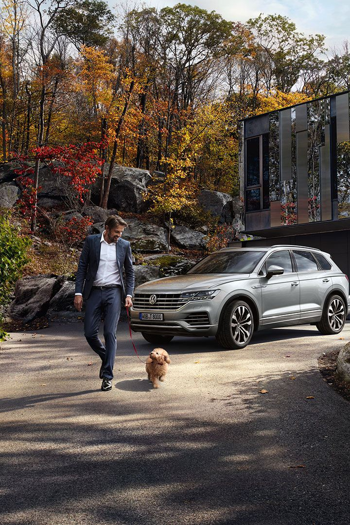 A man and his dog are walking in front of a VW Touareg