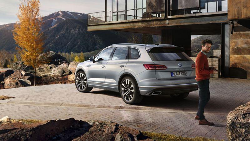 VW Touareg parkt vor einem Hause in den Bergen. Mann geht vom Auto weg.