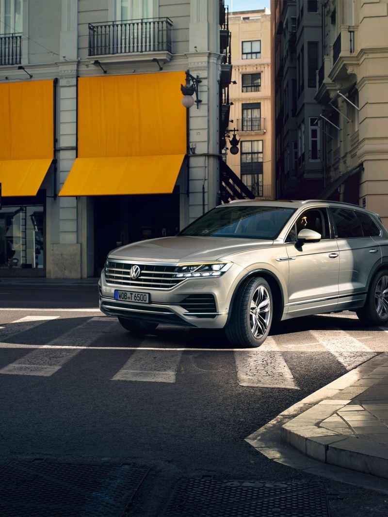 Ein Volkswagen Touareg fährt in einer Stadt um eine Kurve