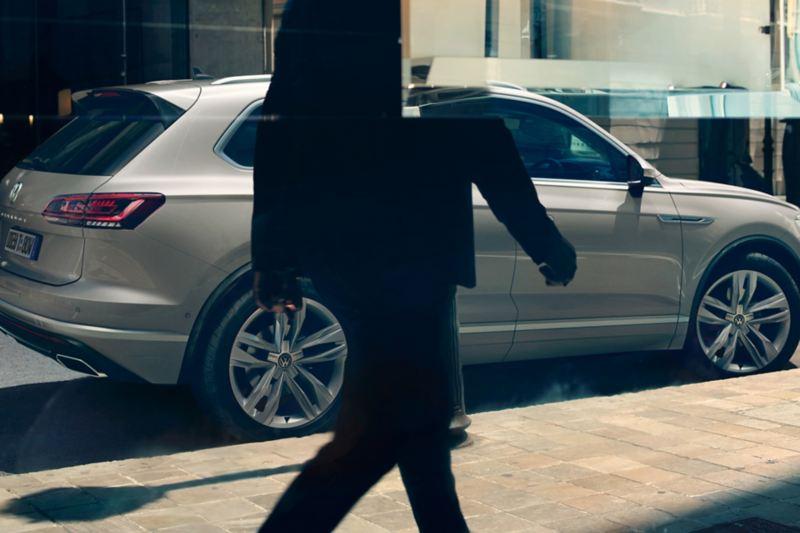 VW Touareg One Million parkt am Straßenrand, davor Silhouette einer gehenden Person und Spiegelung in Scheibe