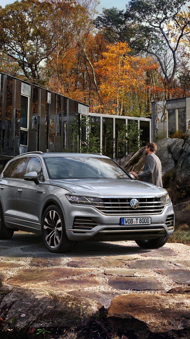 VW Touareg steht vor einem Haus, Mann steht an der Fahrertür, Frau nähert sich dem Fahrzeug von hinten
