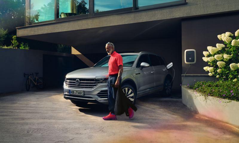 Volkswagen Touareg eHybrid in Silber, Sicht vorne-seitlich, lädt in Einfahrt, Mann geht vorbei