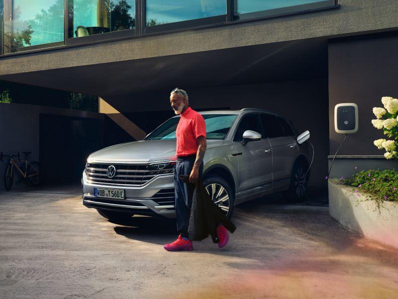 Hõbedane Volkswagen Touareg eHybrid, eest-/külgvaade, laadib sissesõiduteel, mees kõnnib mööda