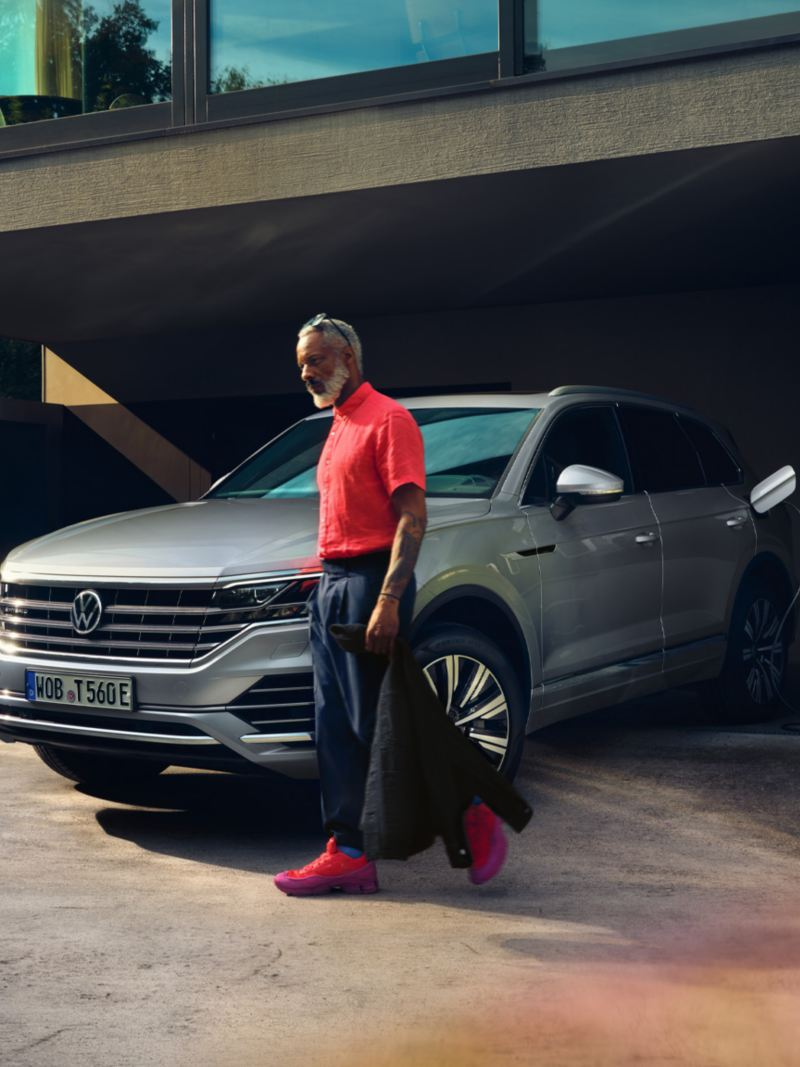 Volkswagen Touareg eHybrid in silver, front-side view, loads into the driveway, man walks past