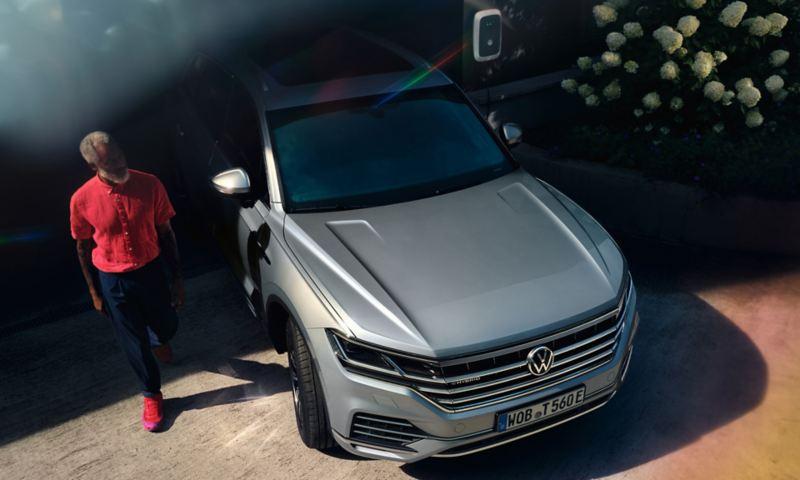 Volkswagen Touareg eHybrid in Silber, Front-Sicht, steht in Einfahrt, Mann geht vorbei