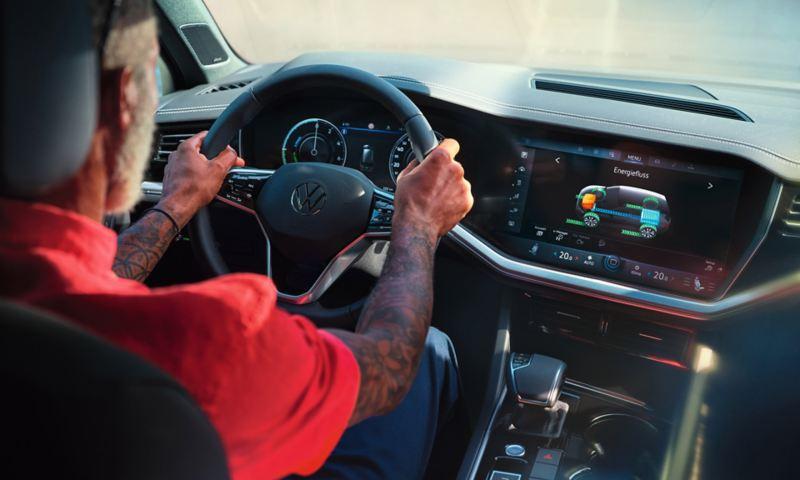 Uomo al volante di Volkswagen Touareg eHYBRID con dettaglio del flusso di energia sul display di infotainment