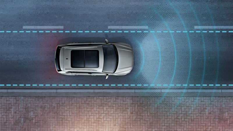 A VW Tiguan seen from above at night, driving on a road. The 'Lane Assist' sensor system is depicted using lines