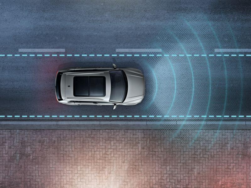 Le Tiguan équipé de Lane Assist roule dans la rue. Capteurs et voie sont représentés graphiquement.
