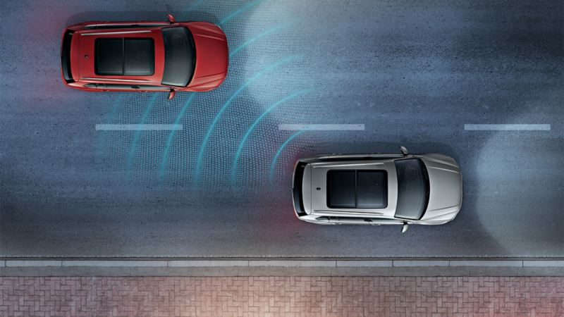 Two Volkswagens driving on a street by night from above. The 'Side Assist' sensor system is depicted using lines