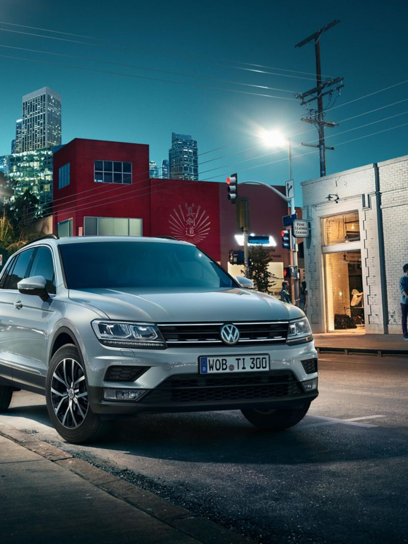 VW Tiguan parking on a road, people standing in front of a shop