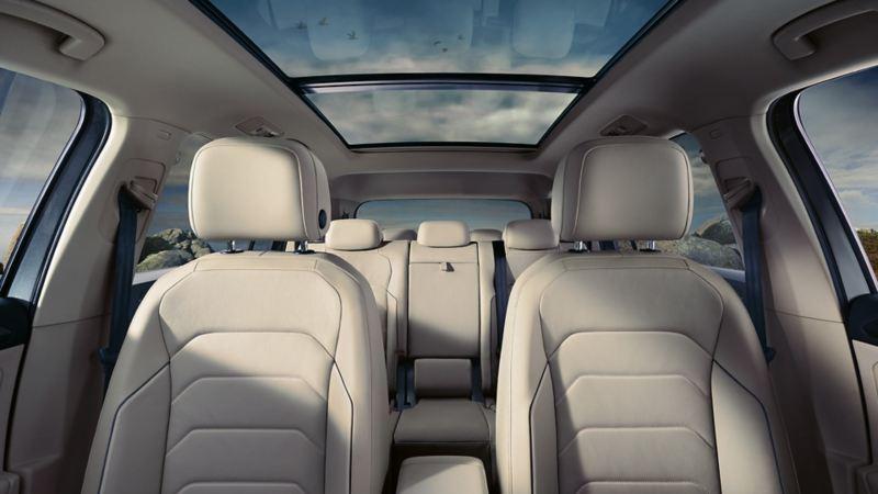 Απεικόνιση ενός Volkswagen Tiguan Allspace που κινείται σε έναν δρόμο, ηχητικά κύματα συμβολίζουν τις κάμερες και τους αισθητήρες