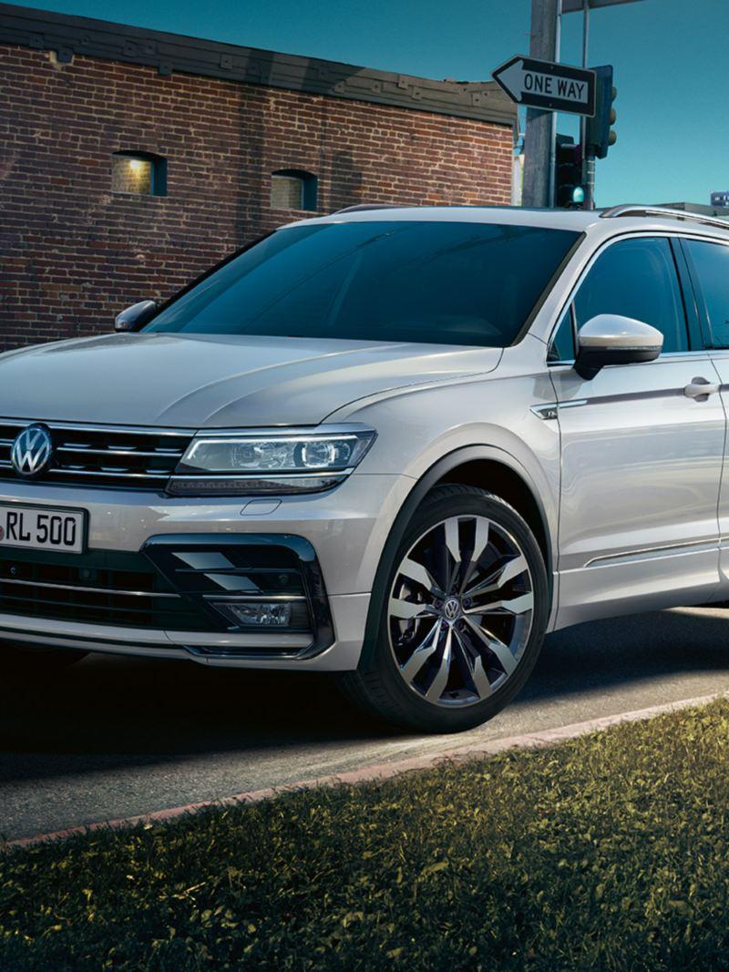 Valkoinen Volkswagen Tiguan kuvattuna kadun varrella kuvattuna etuviistosta.