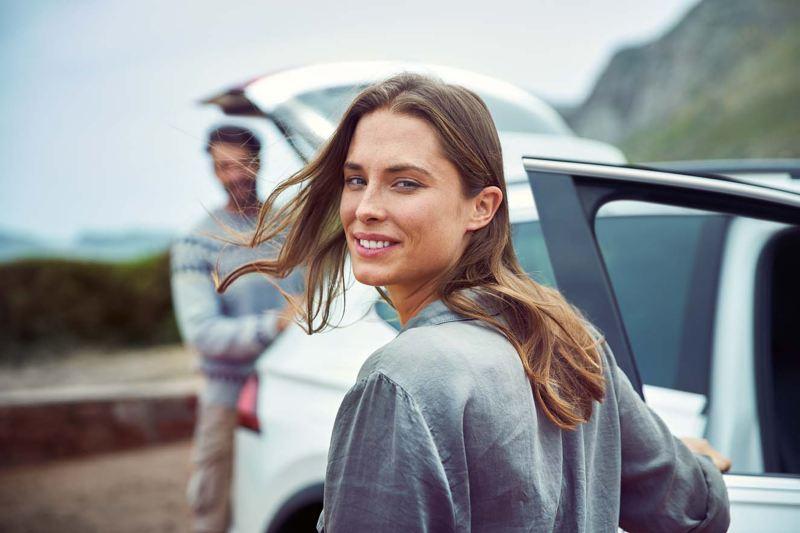 Kvinna och man vid bil med öppen baklucka