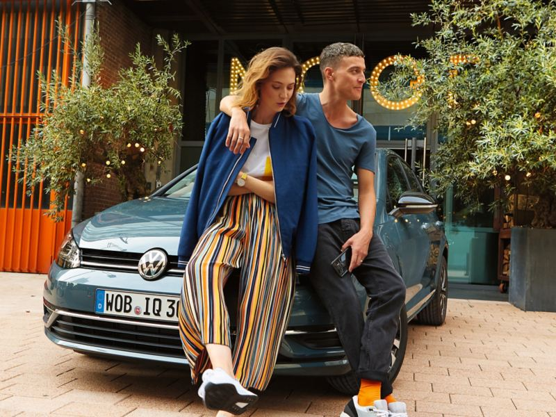2 Personen lehnen an Volkswagen Golf