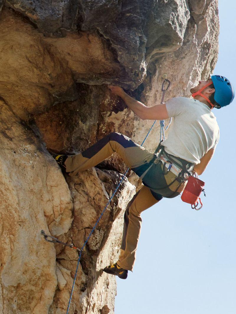 Man climbing a stone wall