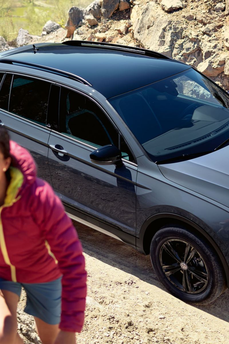 Women climbing a stone wall, VW Tiguan Offroad in the background