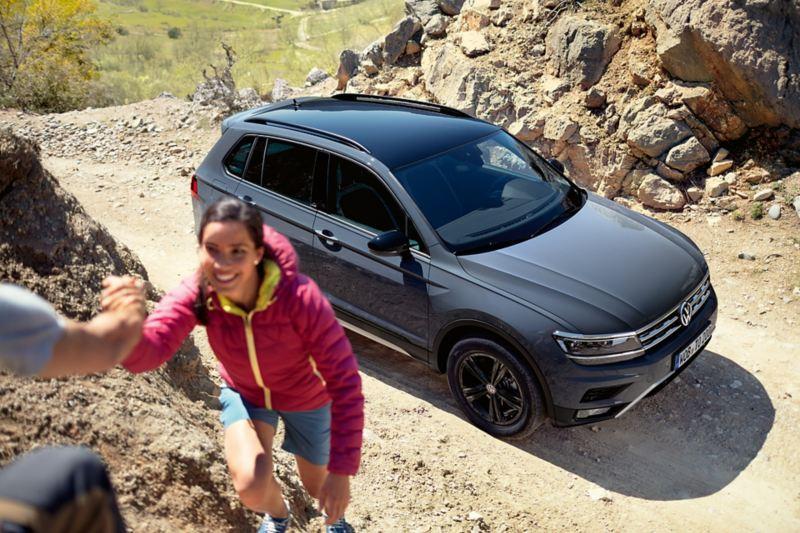 Tiguan OFFROAD ukośnie z góry, kobieta wspina się na skałę