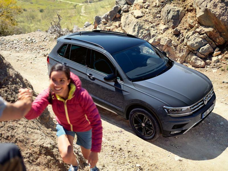 Une VW Tiguan Offroad vue d'en haut, de biais, une femme grimpe sur un rocher.