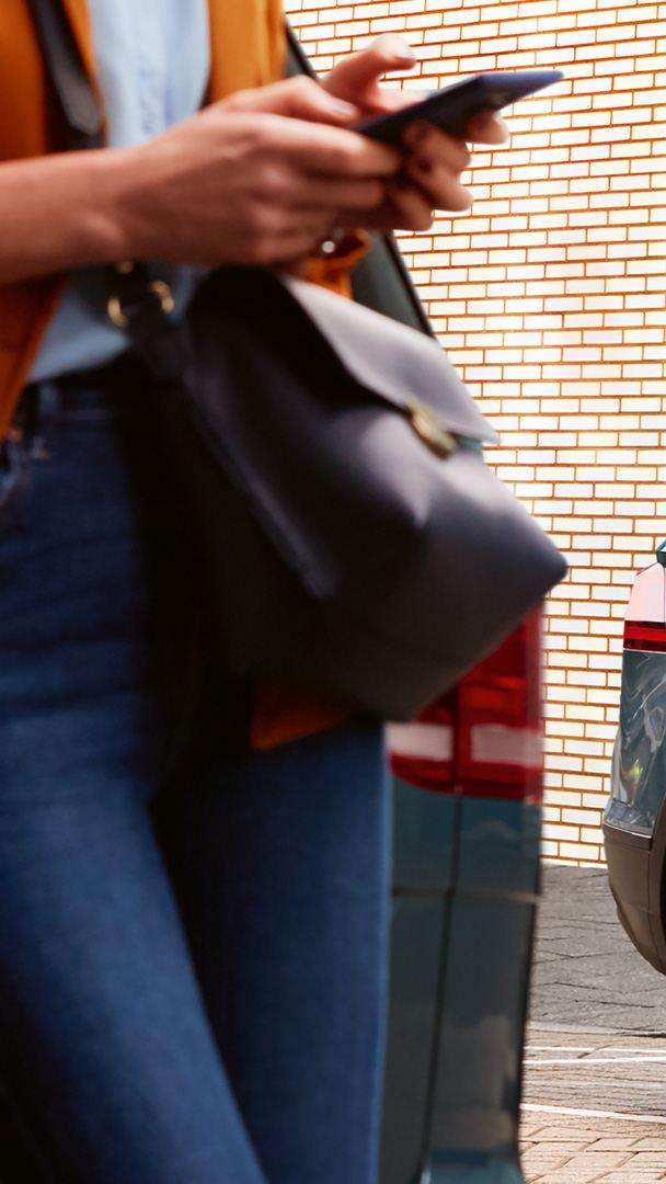 Kvinna står lutad mot Volkswagen