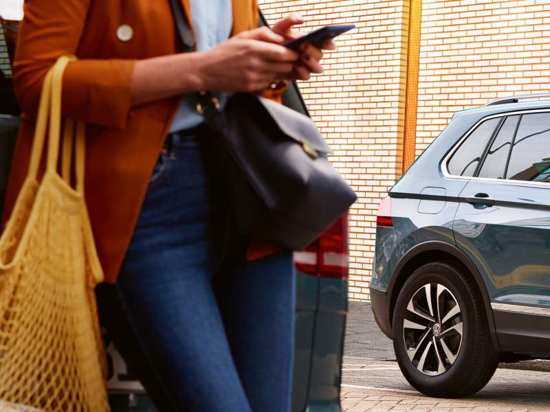 Kvinna med tygkasse står och lutar sig mot en Volkswagen