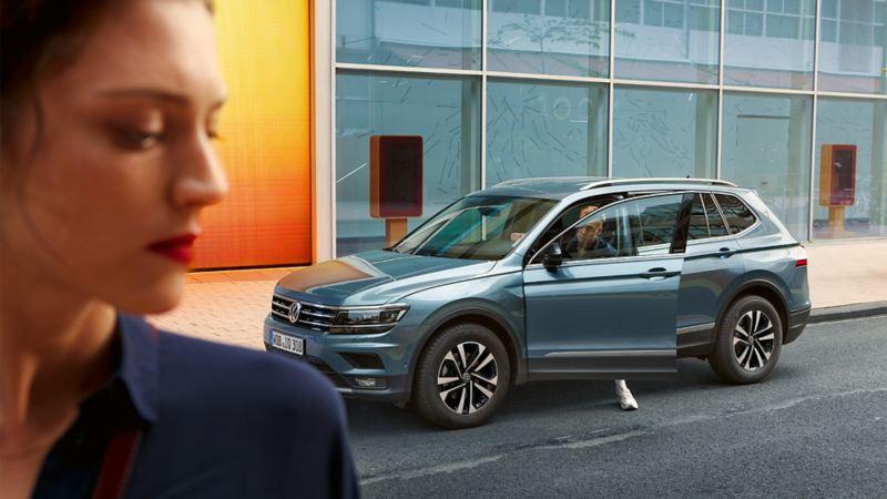 Mann steigt aus dem parkenden Tiguan Allspace IQ. DRIVE aus, Frau ist links im Anschnitt zu sehen