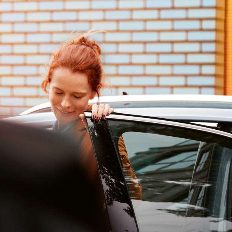 Młoda kobieta wysiada z Tiguana IQ.DRIVE