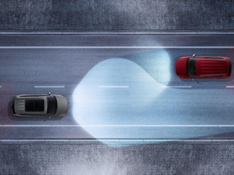 Dans la rue, le Tiguan équipé de Dynamic Light Assist croise d'autres véhicules en sens inverse, vue en plongée.