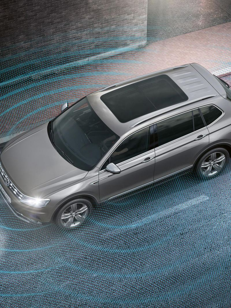 Illustration of a VW Tiguan Allspace driving on a road, sound waves symbolize cameras and sensors