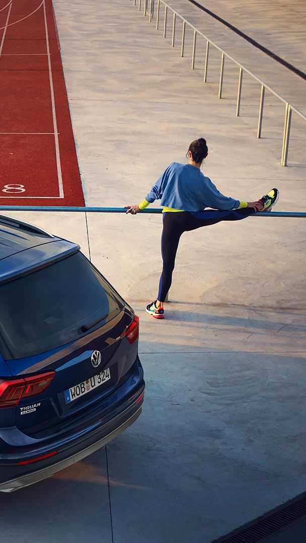 Woman stretching at the side of a tartan track next to Tiguan Allspace UNITED
