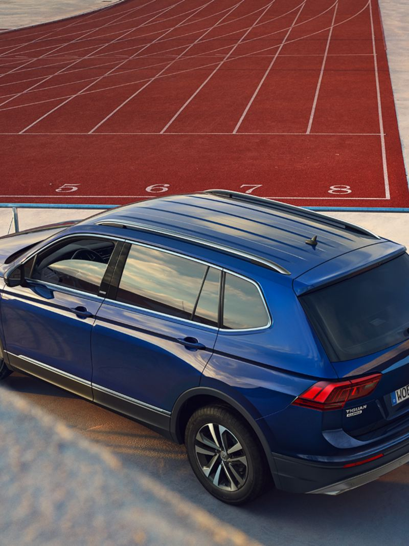 VW Tiguan Allspace UNITED 3/4 rear view with woman stretching in front of tartan track