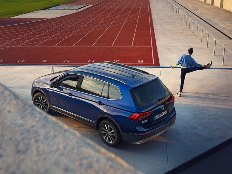 VW Tiguan Allspace 3/4 Heck Mann dehnt sich an Bande von Stadium