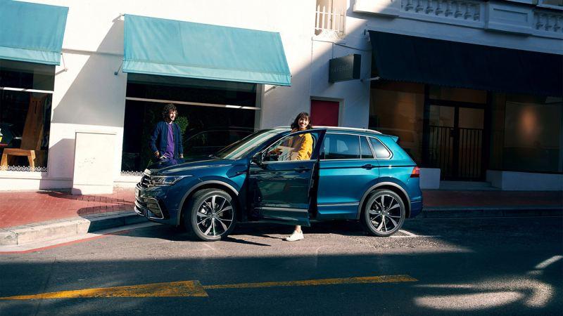 Una donna esce dal lato del conducente da Volkswagen Nuova Tiguan.