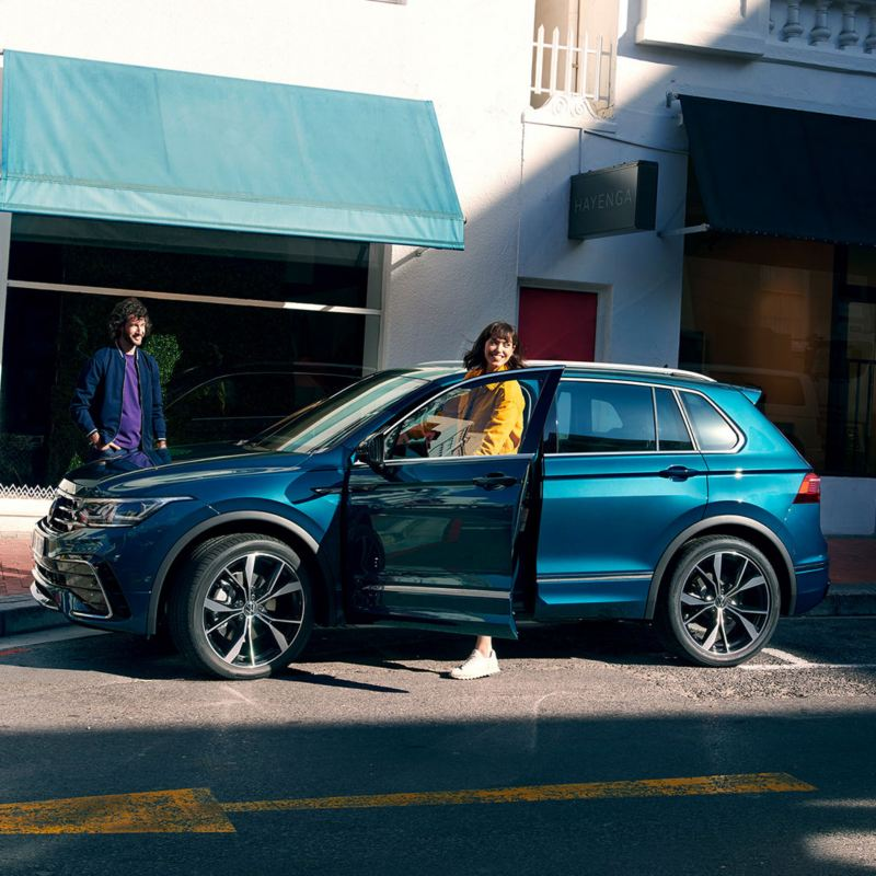 En kvinne går ut av VW Volkswagen Tiguan SUV på førersiden