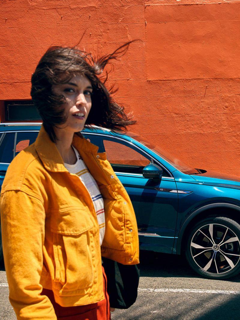 En kvinne med flagrende hår, VW Volkswagen Tiguan SUV i bakgrunnen