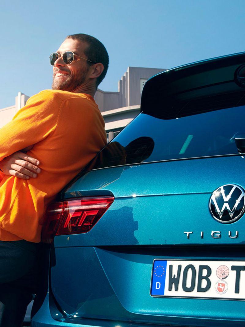 En mann med solbriller lener seg mot bakparten til VW Volkswagen Tiguan SUV