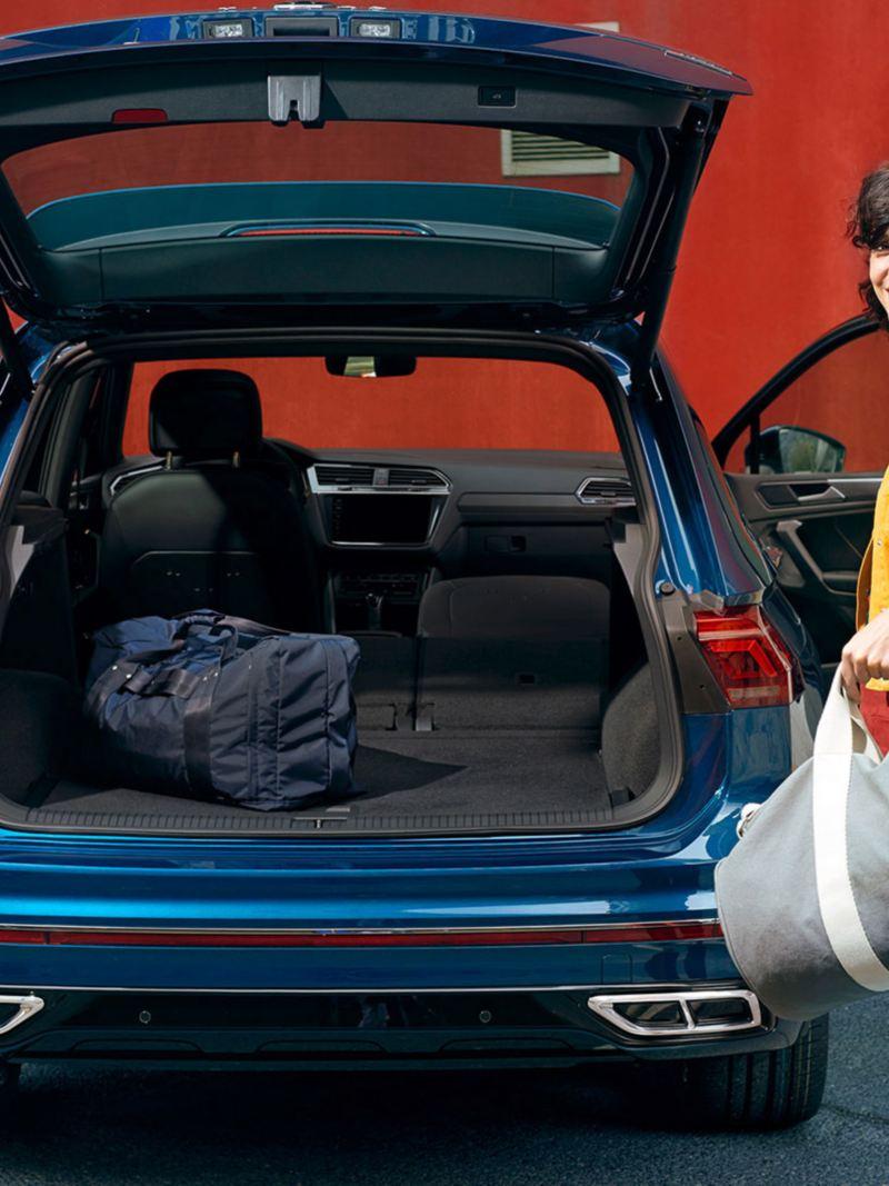 En kvinne med gymbag står ved den åpne bakluken til VW Volkswagen Tiguan SUV