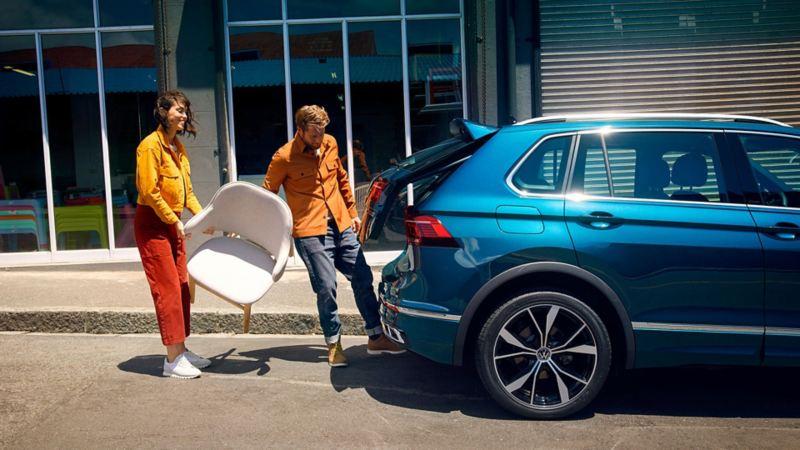 En kvinne og mann løfter en stol inn i bagasjerommet på nye VW Volkswagen Tiguan