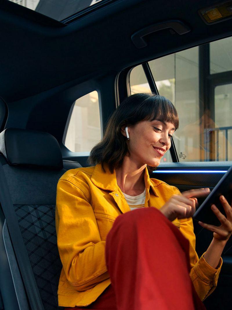 En kvinne med nettbrett i baksetet på VW Volkswagen Tiguan SUV