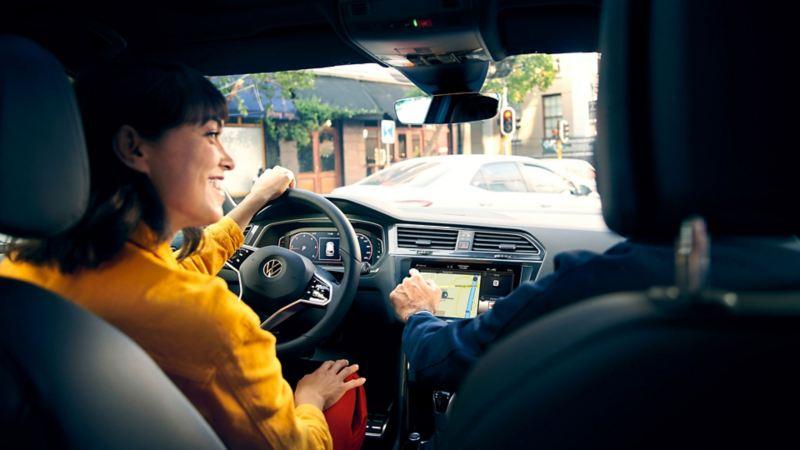 En kvinne smiler i førerseter på VW Volkswagen Tiguan SUV
