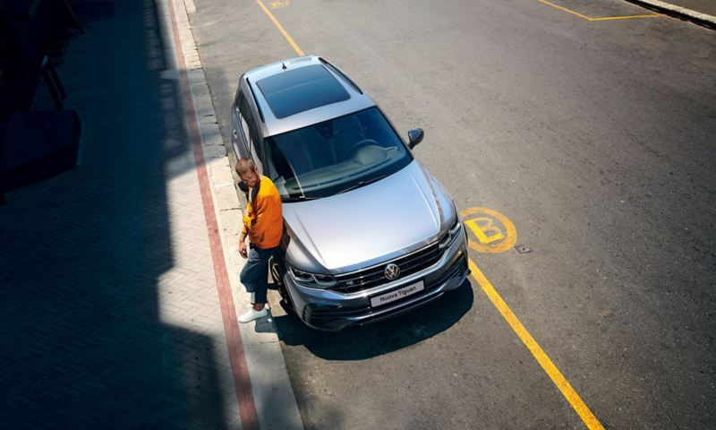 """Un uomo appoggiato a Volkswagen Nuova Tiguan R-Line """"Black Style"""" vista dall'alto"""