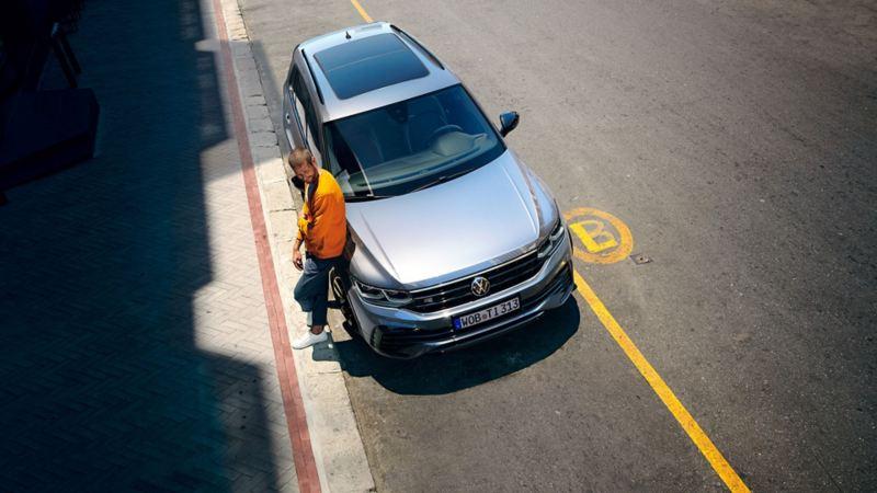 En mann lener seg mot VW Volkswagen Tiguan SUV