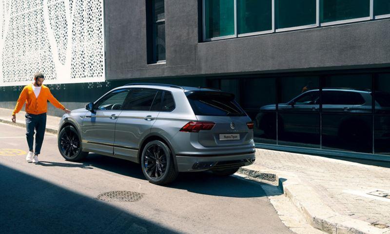 """Uomo tocca cofano di Nuova Tiguan R-Line """"Black Style"""" Volkswagen vista 3/4 posteriore"""