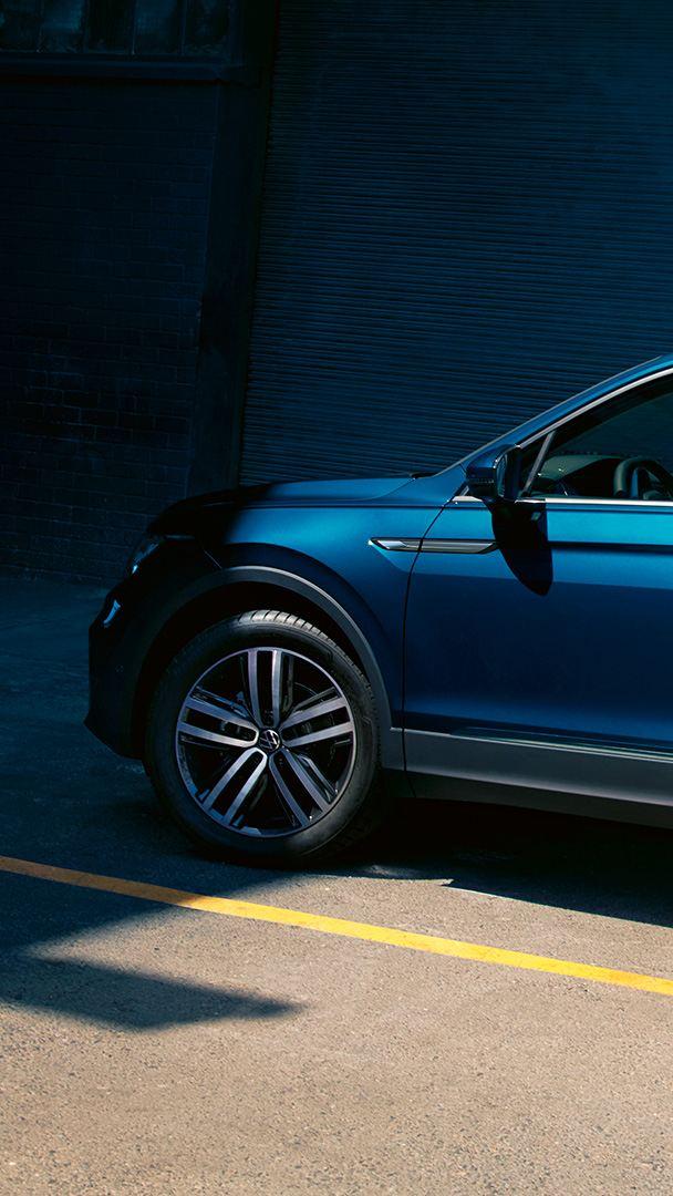 Blauer VW Tiguan in Innenstadt geparkt, Frau geht lachend vorbei. We Connect.
