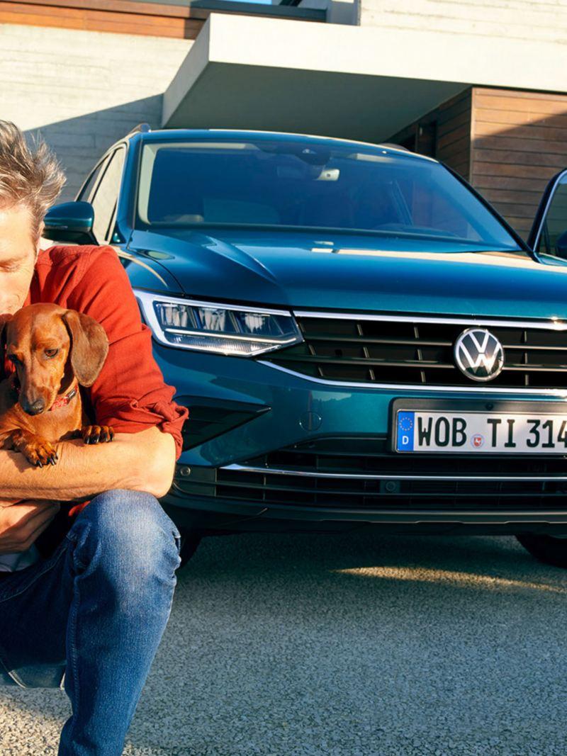 En mann med dachs hund foran fronten til en VW Volkswagen Tiguan SUV