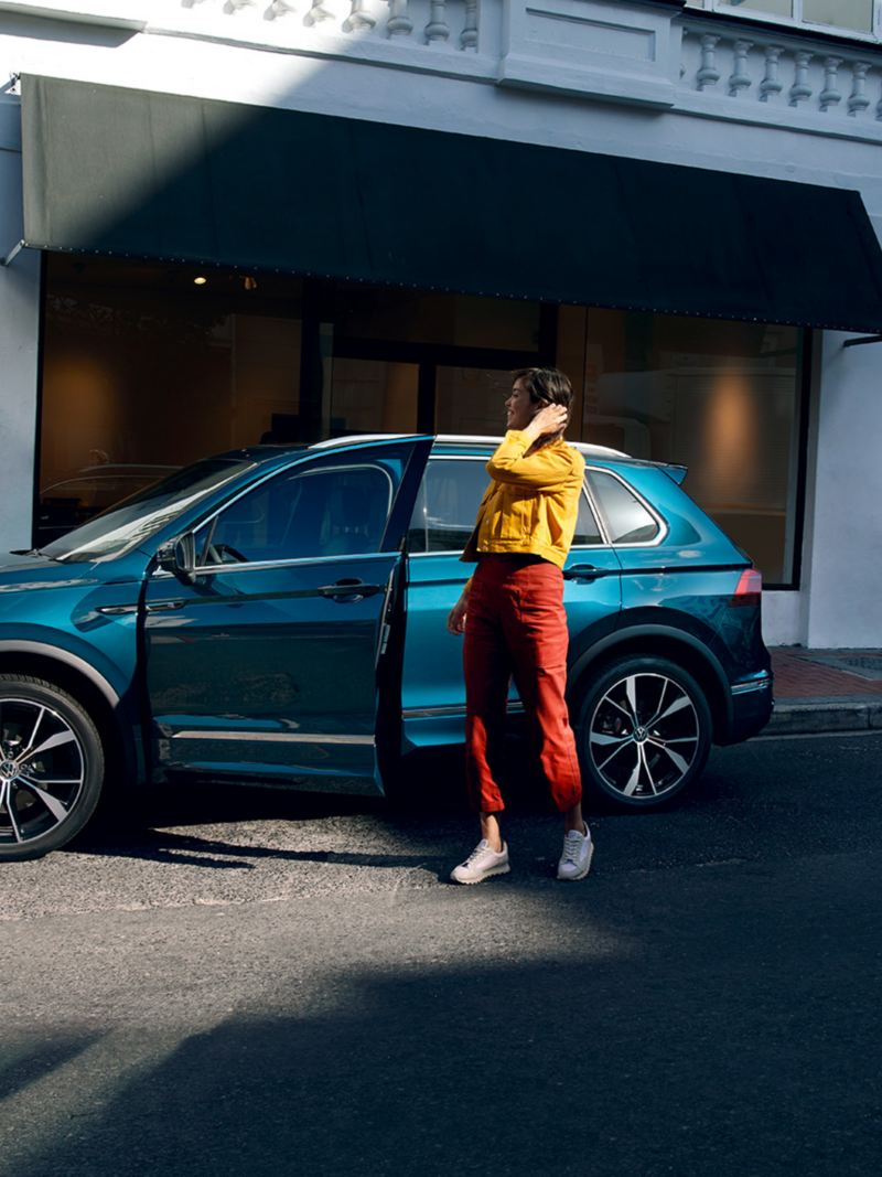 Woman at the open driver's door of a VW Tiguan