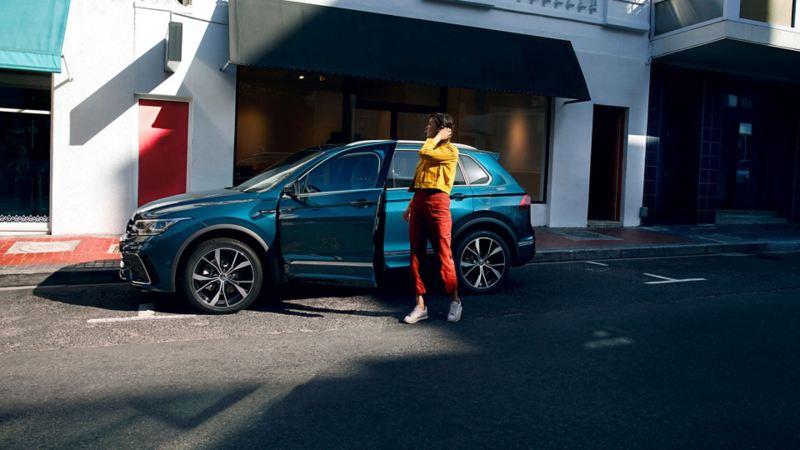 En kvinne står ved døren åpen på Volkswagen VW Tiguan SUV